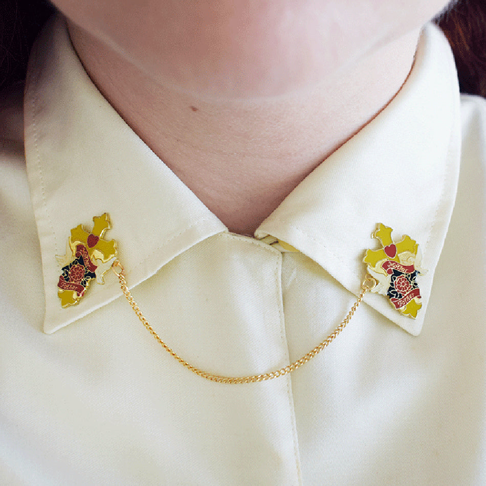 This collar clip is shown attached to a white shirt collar. The collar clips are the same, two gold goth crosses attached by a gold chain. By Lydia Jones.