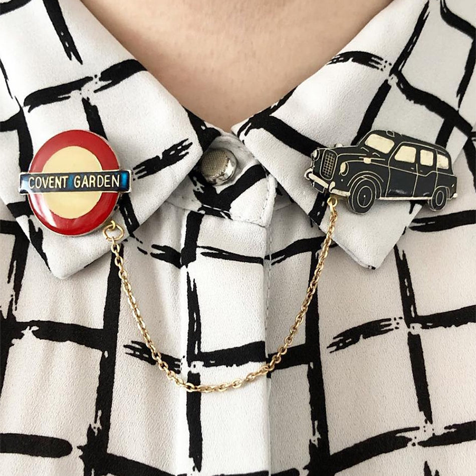 "These two collar clips are attached to a white shirt with black squares. The collar clip on the left is that of the iconic London underground sign saying ""Covent Garden"" and on the right side is a black London cab. Each clip is attached by a gold chain across the collar. By Lydia Jones."