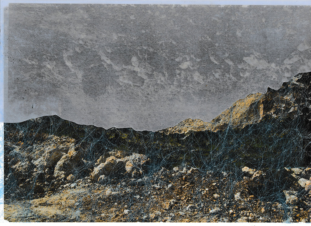 This is a photographic print, which presents a landscape. The upper half of the photo is taken up by a black and white sky with think clouds. The bottom half depicts barren rock with luminous blue veins running across it. By Maria Makridis.