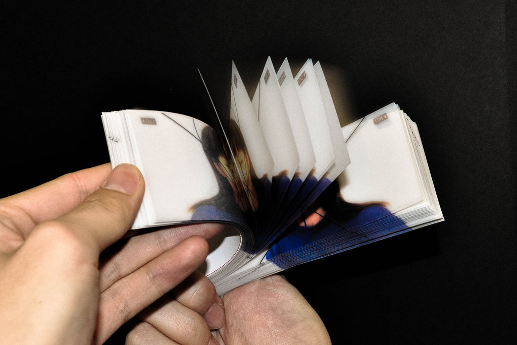Another photo of the pocket book held in hands with the pages being flicked. By Django (Jiangge) Cai