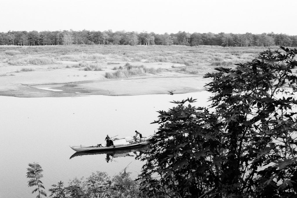 A photograph by Sophia Wöhleke depicting a river opening side on, a boat in the river is fishing and about to pass out of view behind some trees, the image is in balck and white.