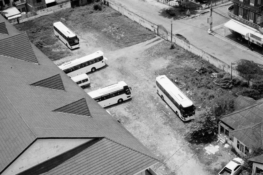 A photograph by Sophia Wöhleke depicts a view high up looking over the roof and car park of a coach garage in one of the countries Sophia visited. This image is in black and white.