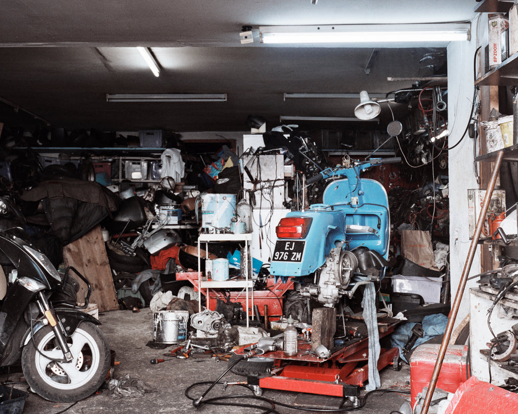 This image depicts a dark busy mechanic's garage or workshop. The space is filled with a variety of objects from paint cans, repair tools and cables. there is a blue vespa on the right hand side that is in the process of being repaired. By Sophia Wohleke.