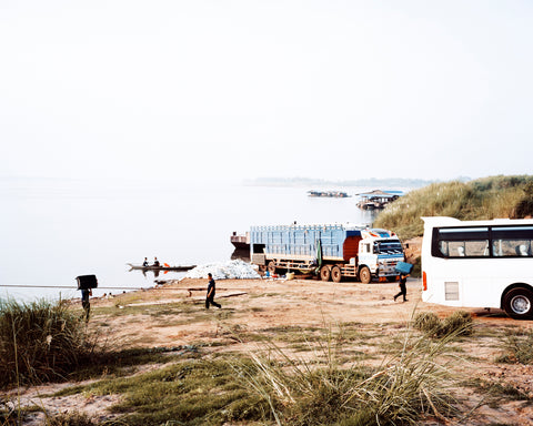 This image depicts a beach car park, with a background of the sea and a few little rocks. There are one or two people running across the beach to and from a coach. By Sophia Wöhleke.