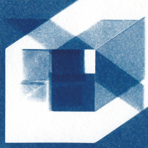 "Cyanotype print of blueprint architectural ""axonometric"" drawings.  The image depicts a clear acrylic block with shadows and reflected light of each unique arrangement. The colours in the print are blue and white. By Eleanor Suess."