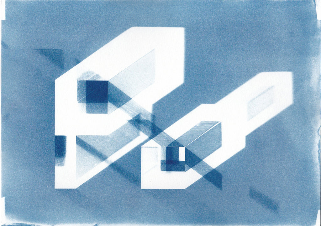"Cyanotype print of blueprint architectural ""axonometric"" drawings.  The image depicts clear acrylic blocks with shadows and reflected light of each unique arrangement. The colours in the print are blue and white. By Eleanor Suess."