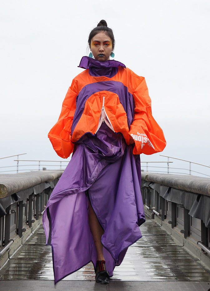 Orange and purple top with white zip detail, purple hemming, and a high neck line. Created from an upcycled tent. Piece by Amber Kim