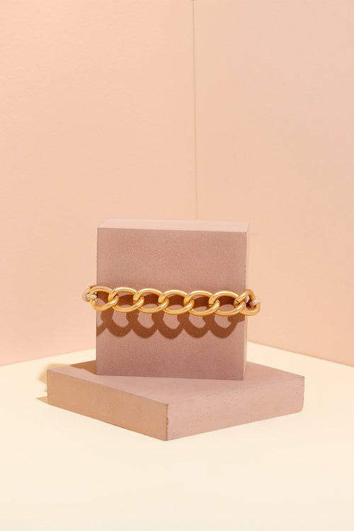 The Hair Edit Soft Gold Chain Wrap Metal Hair Tie on Pink Jewelry Display