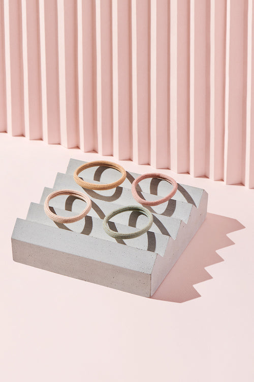 The Hair Edit gilded threads gold accented set of four hair ties on cement display