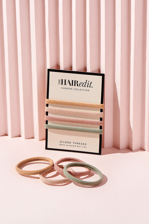 The Hair Edit gilded threads gold accented set of four hair ties in packaging & on pink display