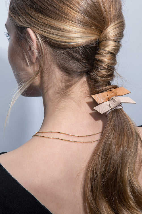 The Hair Edit Vegan Faux Leather Hair Tie Bow Accessories Set of 3 Ties in Beige & Brown Colors styled on twisted ponytail of blonde haired female model close-up