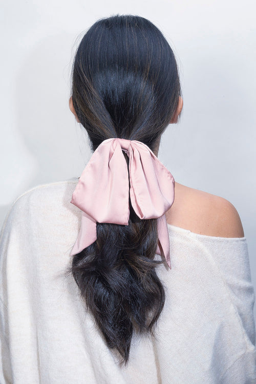 The Hair Edit Soft Blush Pink Oversized Ribbon Scrunchie Bow Hair Tie worn in ponytail by black wavy haired female model