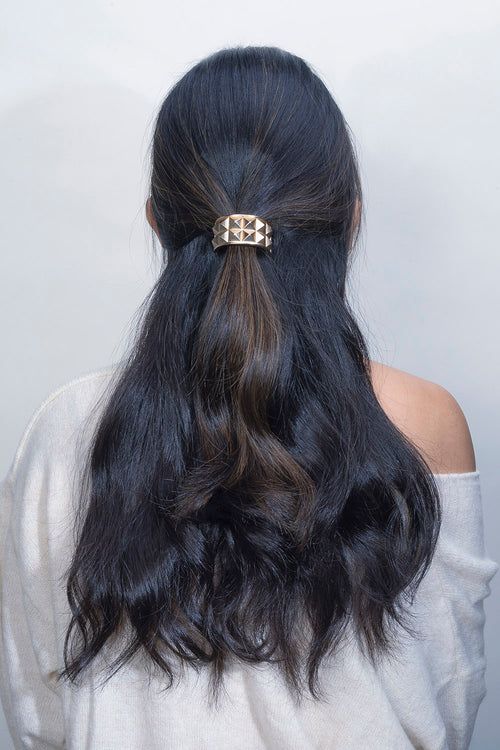 The Hair Edit Soft Gold Pyramid Studded Hair Cuff Textured Metal Hair Tie worn by black wavy haired female model