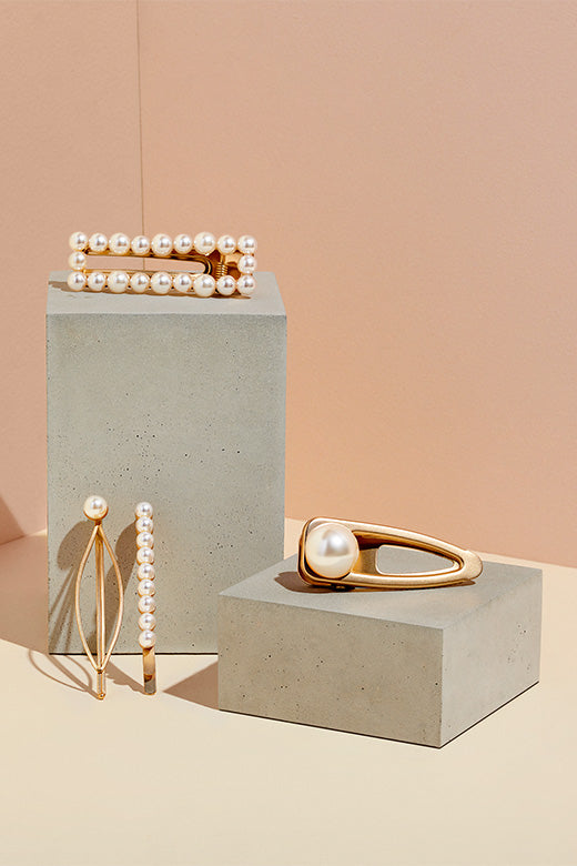 The Hair Edit's Pearl & Gold Jeweled Clips & Pins Hair Accessories on cement block display