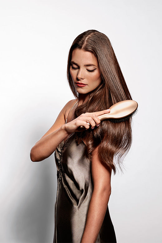 Brunette female model brushing her hair with the Detangling & Smoothing Gold Hairbrush by The Hair Edit with right hand