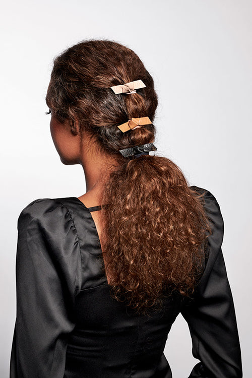 The Hair Edit Vegan Faux Leather Hair Tie Bow Accessories Set of 3 Ties in Black, Beige & Brown Colors styled on ponytail of brunette curly haired female model