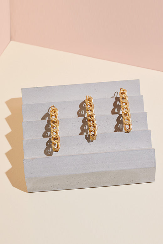 The Hair Edit Soft Gold Chain Link Cable Barrette Hair Clip Accessories display of 3 clips on cement block