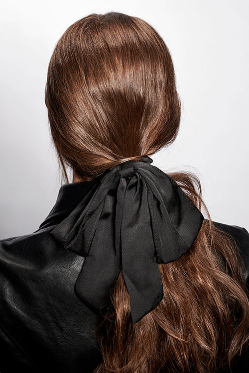 The Hair Edit black oversized ribbon hair scrunchie worn by wavy haired brunette model with ponytail