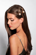 Long haired brunette female model wearing The Hair Edit's pearl gold hair clip accessory