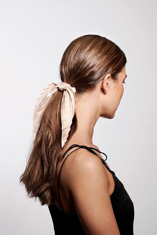 The Hair Edit cream colored pleated ribbon scrunchie hair tie worn by long haired brunette model with ponytail