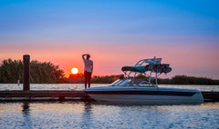 Boat with wakeboard tower docked at sunset.