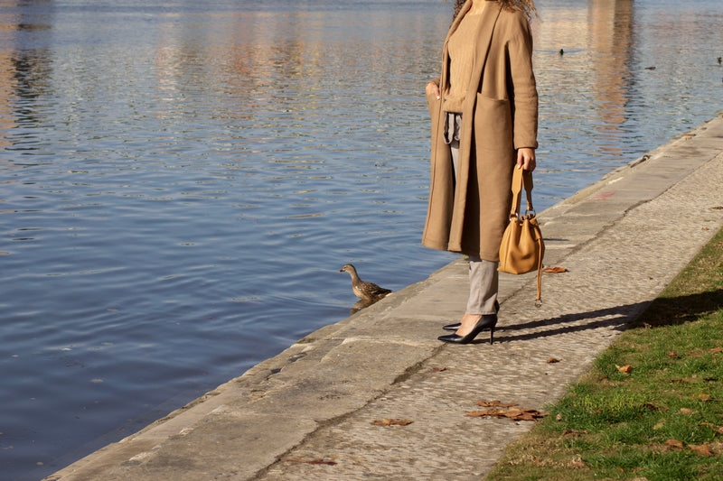 Model carring a leather bucket bag in tan color near a lake