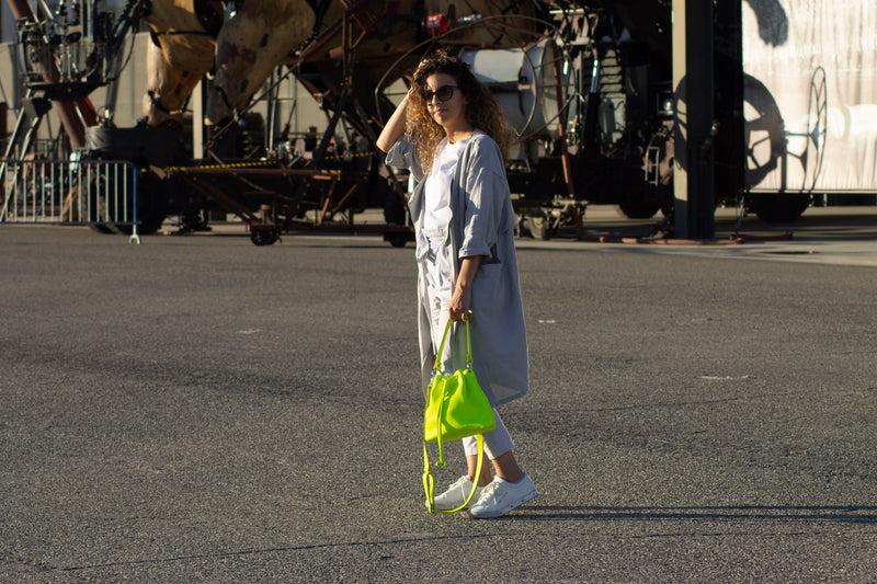 Model carrying leather bucket bag in yellow neon