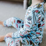 Smiling baby sitting on the couch playing with toys and wearing pajamas