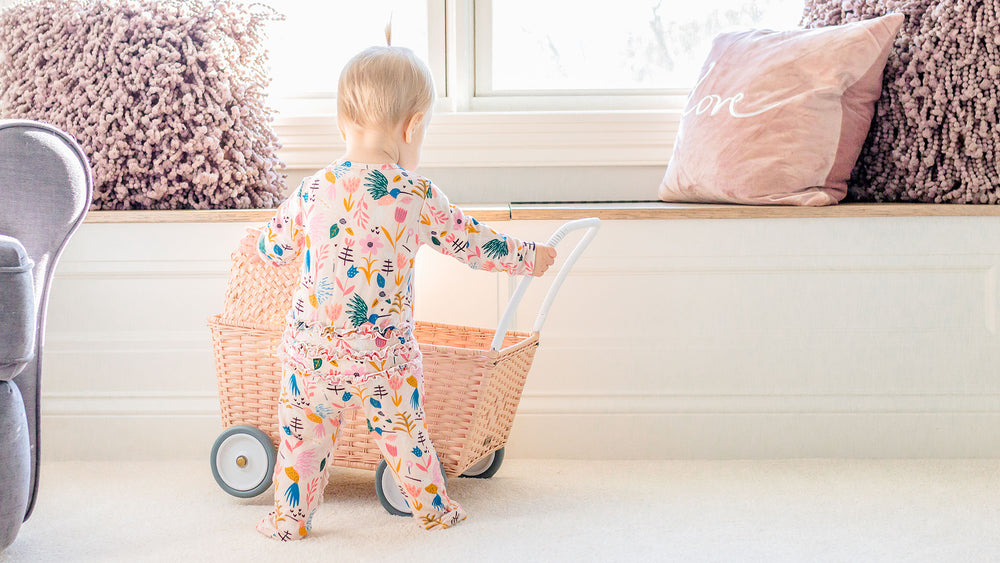 toddler playing with a shopping cart, photo taken from behind showing bamboo apparel