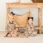 two toddlers wearing wild child footies bamboo apparel playing with toys