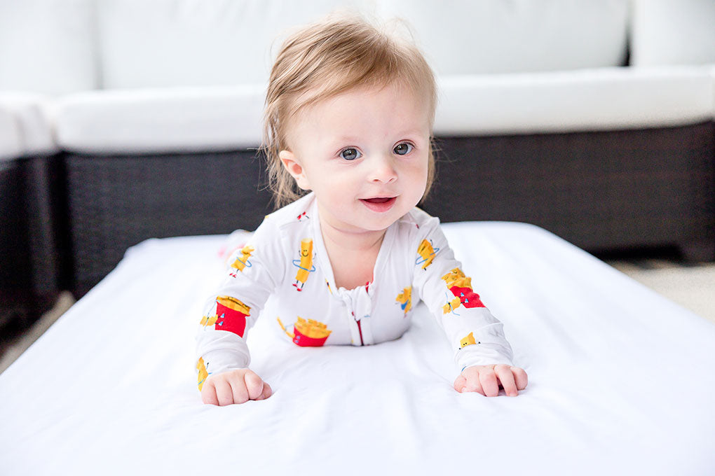 smiling baby with blue eyes on a mattress featuring bamboo apparel