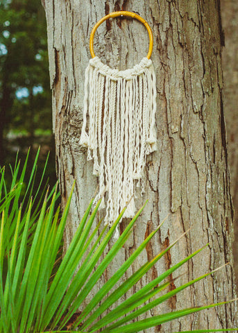 Rattan hoop with rope fringe hanging on a tree by SoulMakes