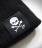 Outcast Black Slouch Beanie Flat close up of black embroidered skull icon tag