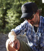 Outcast black foam trucker cap on guy in campsite