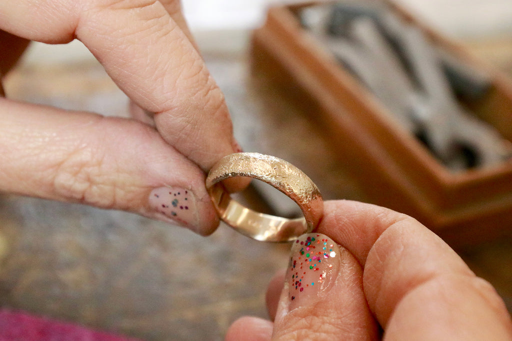 Close-up of Betsy holding ring on jewelry bench