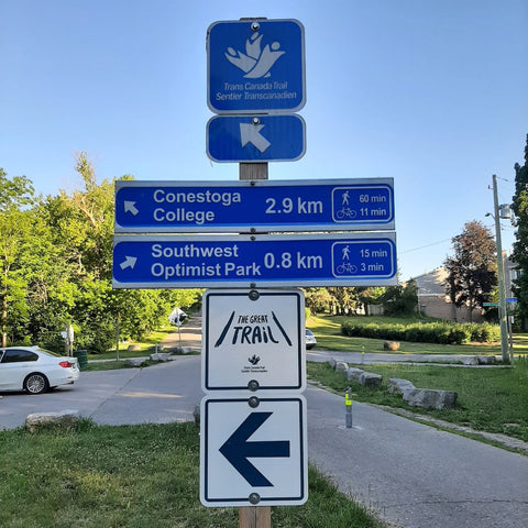 photo of signpost showing directional arrow for Trans-Canada Trail, Conestoga College and Southwest Optimist Park distances and walking and biking time