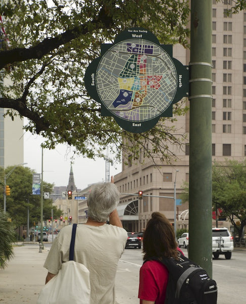 Two people looking up at a circular wayfinding map of San Antonio affixed on a lamp-post. Shows cardinal direction and neighbourhoods in different colours