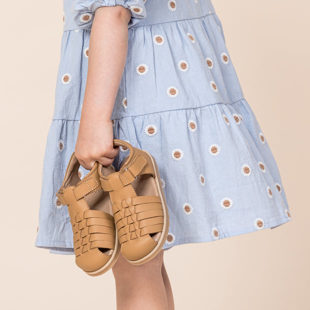 Toddler girl holding pretty brave tan sandals