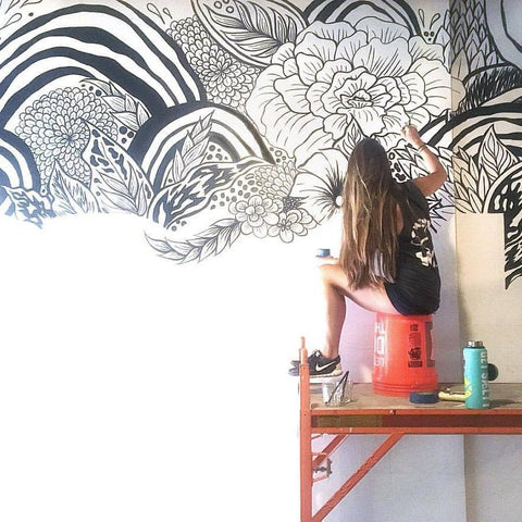Photo of Kasi Turbin Painting a Black and White Mural