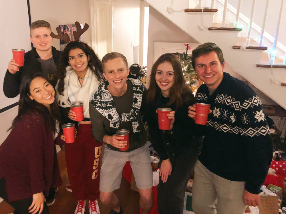 six friends holding red party cups at a christmas party