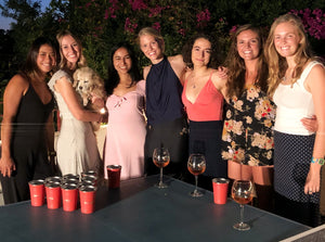 seven women smiling in front of beer pong table
