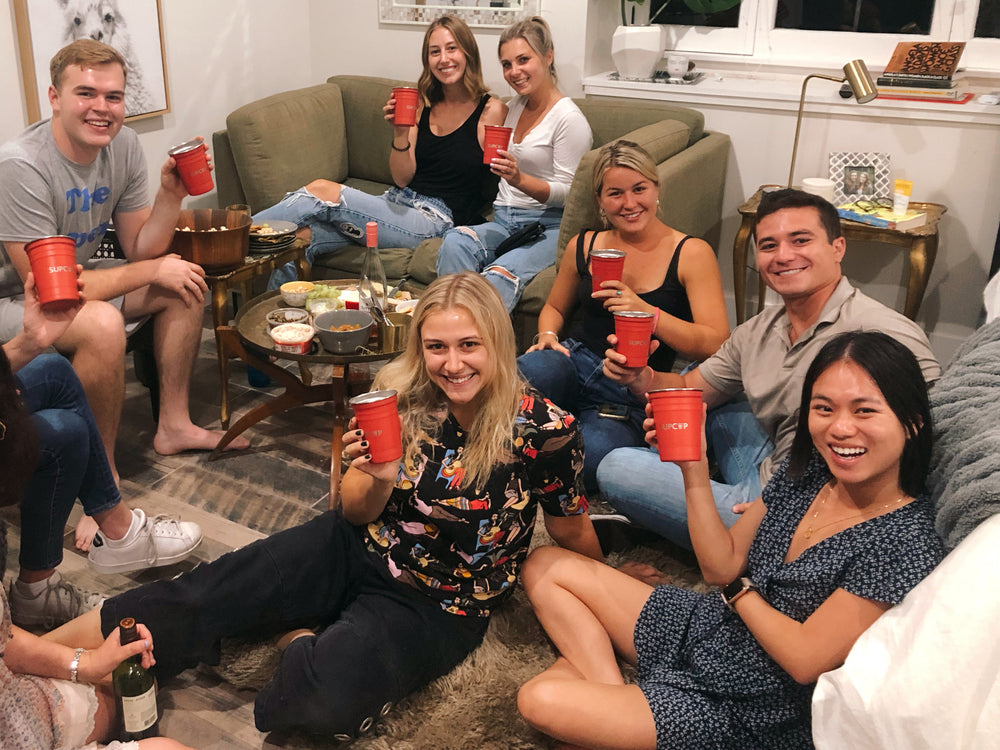 seven friends at a wine and cheese night holding supcups