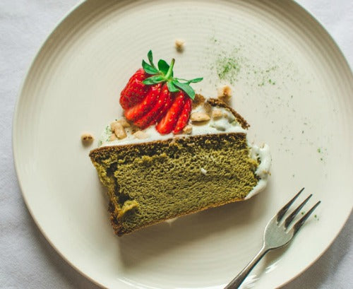 Matcha green tea cake with vanilla yoghurt frosting, topped with strawberry and nuts