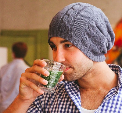 Guy with a beanie drinking matcha tea that he made with an electric whisk