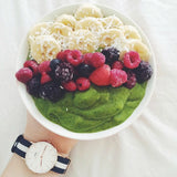 Matcha mango spinach smothie bowl with banana and berries topping