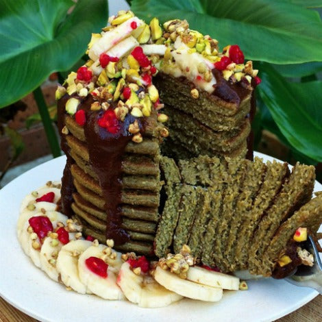 cut-up matcha green tea pancakes stack topped with banana, berries, nuts, coconuts and chocolate sauce