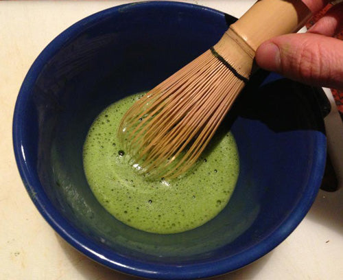 Matcha tea with layer of froth and bamboo whisk