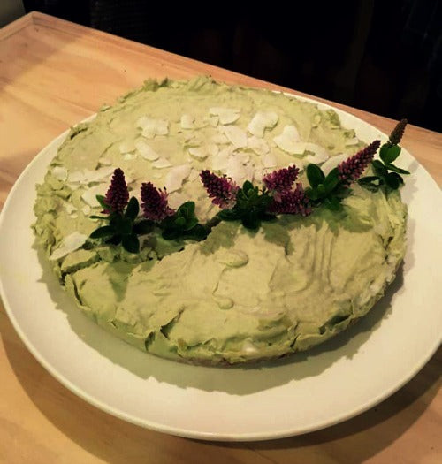 Matcha Green Tea Lime Vegan Cake, with no sugar or dairy added. It's topped with coconut chips, lime zest and flowers