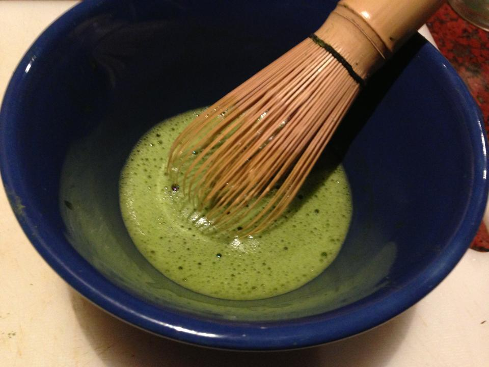 whisking matcha tea in bowl