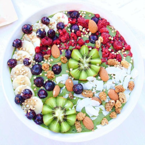 Delicious healthy Matcha Spinach Avo Vegan Smoothie Bowl topped with fresh fruits, berries, kiwis, nuts, or any choice of toppings